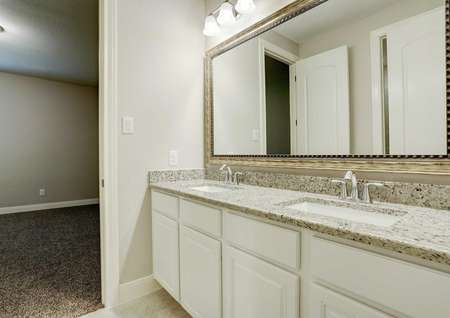 Bradley bathroom with dual-sink vanity, framed mirror, and wall-mounted light fixure