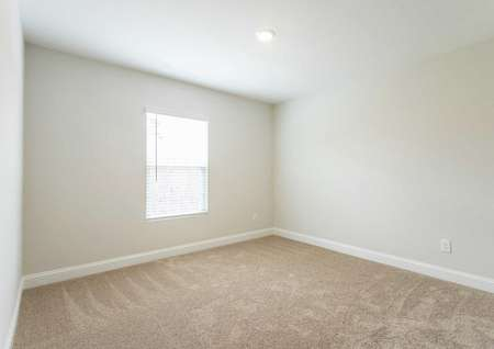Hartford bedroom with tan carpet, white trim, and window