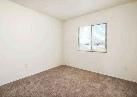 The Alamo floor plan second bedroom shown carpeted with a window with blinds.