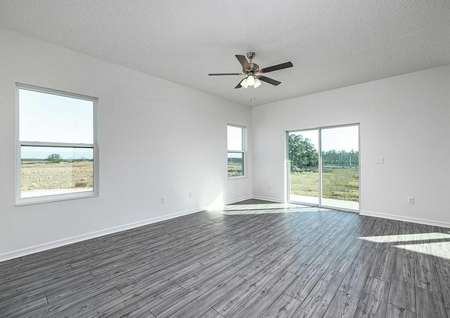 Large family room with luxury vinyl plan flooring and windows letting in natural sunlight.