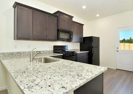 Aspen kitchen with light colored granite counters, undermount sink, and custom brown cabinets