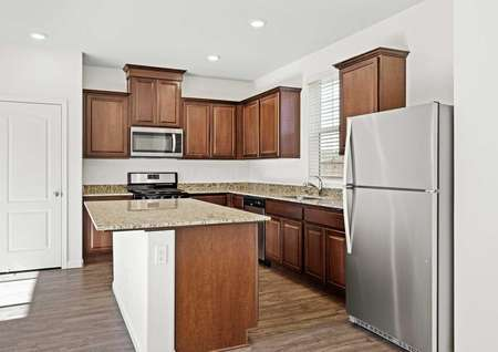 Chef-ready kitchen with stainless steel appliances, brown cabinets with crown molding detail and granite countertops.