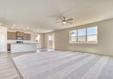 Wide view of the Jasmine floor plan living, dining and kitchen area with a ceiling fan and recessed lighting.
