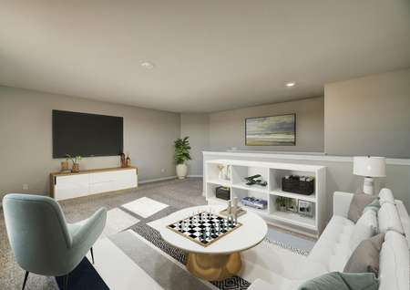 Staged game room with white couch, white cabinet and televsion.
