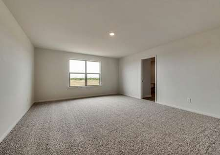 The spacious master suite has bright windows, white walls and brown carpet.