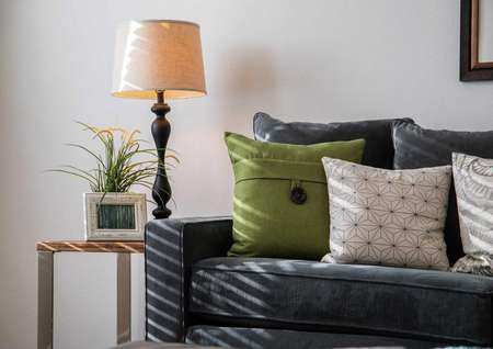 Model home with dark blue sofa that has green and white pillows, framed picture hanging on the wall, and lamp with beige shade in the corner
