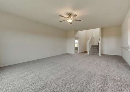 The living room has brown carpet, white walls and comes with a ceiling fan installed.