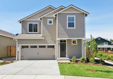 Larch two-story home with brown siding and white trim, 2 car carriage style garage door, and green grass with a tree in the front yard