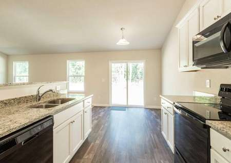 Alexander kitchen with white cabinets, black appliances, and wooden flooring
