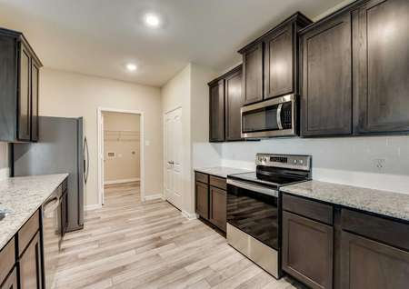 Modern wood cabinets, granite countertops and new appliances in the Houghton floor plan's kitchen.