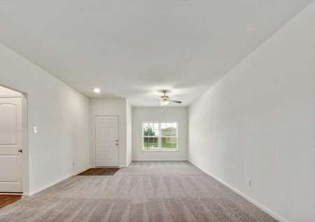 Travis front room with window, ceiling fan, and tan carpets