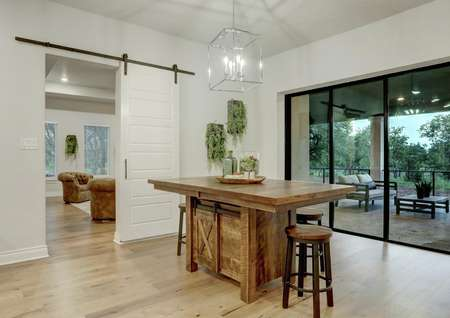 Staged breakfast area with wooden table, gorgeous lighting and back yard views.