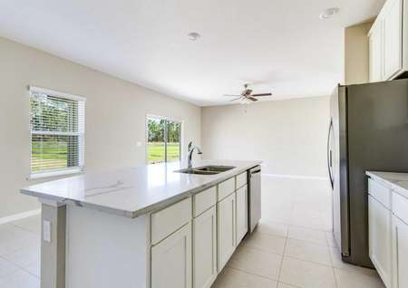The St. Johns floor plans kitchen that has an island, white cabinets, tile flooring and stainless steel appliances.