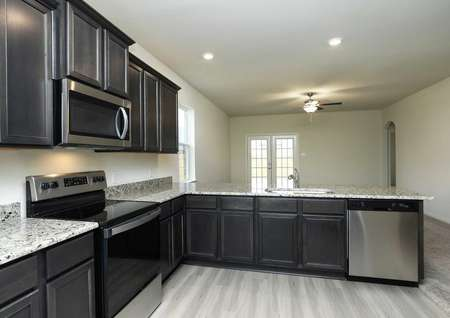 polished granite counters with drark brown cabinetry and stainless steel electric range with microwave over it