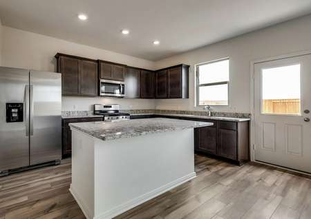 The stunning kitchen has stainless steel appliances, brown cabinetry and granite countertops with a large island.