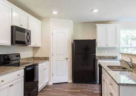 Avery floorplan kitchen with white cabinets and black appliances