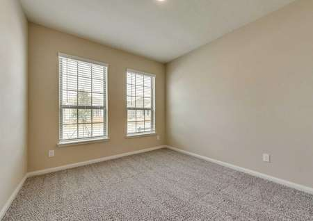 Erie secondary bedroom with two large windows and carpet