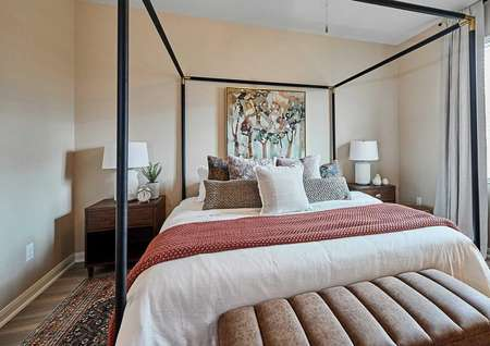 Staged bedroom with decorations and bed side tables.