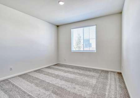 A spare bedroom in the Sunflower floor plan with light brown carpet, white baseboards and walls with a window on one of them.