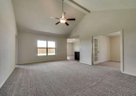 Sabine new home plan family room with ceiling fan, brown carpeting, and glass French doors