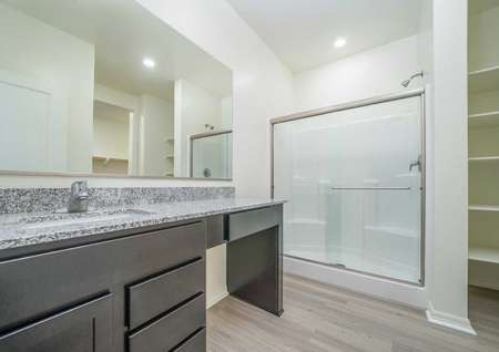 Laguna bathroom with granite countertop, brown cabinets with makeup desk, and walk in shower