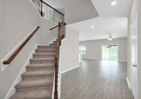 Entrance view of spacious home with stairs leading to the second floor of a two-story home.