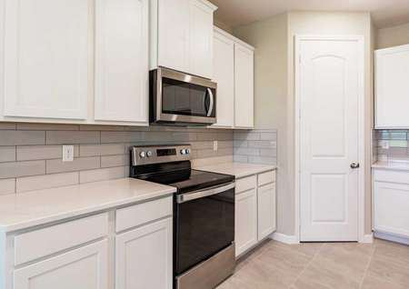 The kitchen with a small pantry, white cabinets, quartz countertops and tile flooring in the Sorrento floor plan.