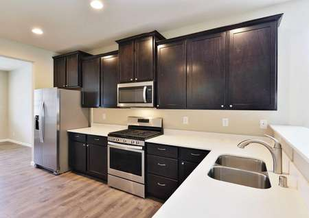 Columbia kitchen with white countertops, brown cabinets, and overhead recessed lights