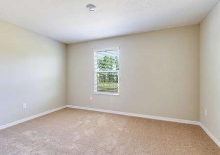 The Tomoka plan's secondary bedroom with light brown carpet, white baseboards, tan walls and a window.