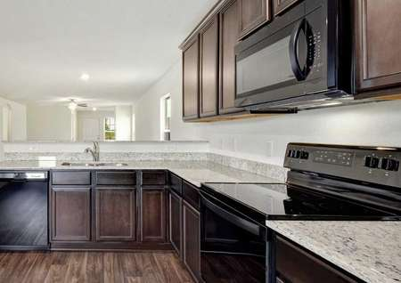 Hawthorn kitchen with dark brown wood cabinetry, tiled floors, and black appliances
