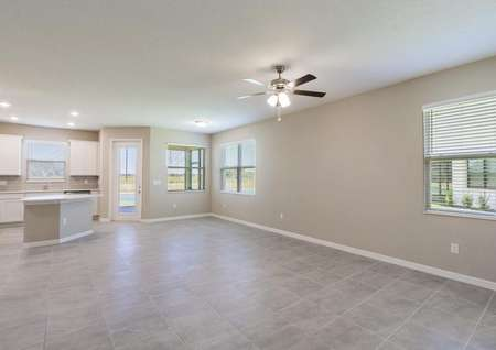 The spacious living and dining area in the Tuscany floor plan has tile floors, multiple windows and a ceiling fan with lights.