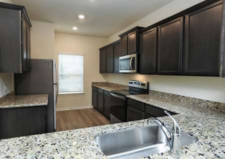 view of kitchen from breakfast bar, granite counters, stainless electric range, builtin microwave, refrigerator and window