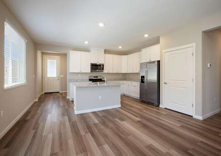 The kitchen is open to the living room and has white cabinets, granite countertops and wood style flooring.