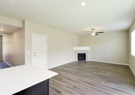 The Northwest Cypress living room is shown with vinyl wood like flooring and corner fireplace, lots of natural lighting.