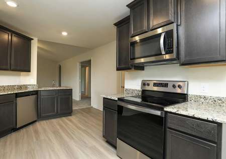 kitchen with granite, stainless electric range, built-in microwave, pale flooring looks into living room
