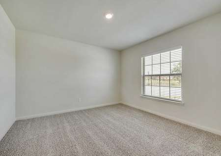 A bedroom in the Wichita model. One large window with blinds, brown carpet, white walls and white baseboards