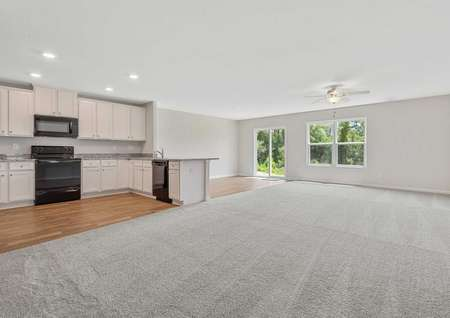 Allatoona great room with light grey carpeting, white cabinetry, and black appliances