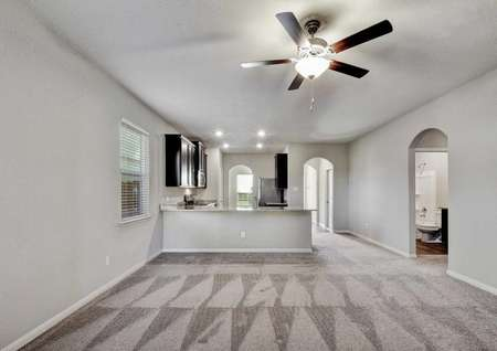 Fannin completed great room with brown carpet floors, gray walls with white trim, and a brown overhead ceiling fan