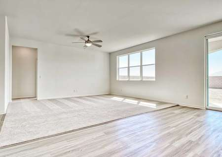 Aster great room with carpet in the family room, hardwood floors in the dining room, and large backyard window