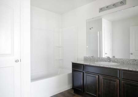 Hennepin bathroom with granite counters, white on white fixtures, and brown cabinets