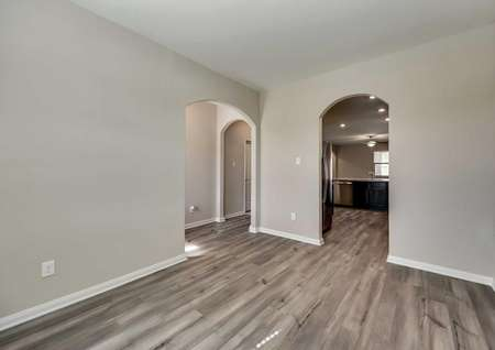 Maple dining area with arched entryways, white trim on the walls, and ceramic wood-like flooring throughout
