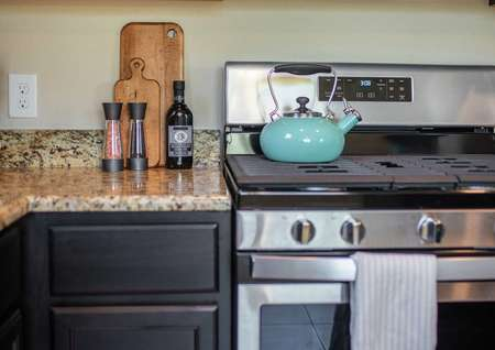 Kitchen staged with turquoise teapot, salt and pepper shaker, and cookie jar on countertop