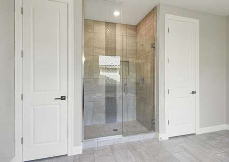 Hawley master bath with built-in shower with glass panels, storage closets, and ceramic floor