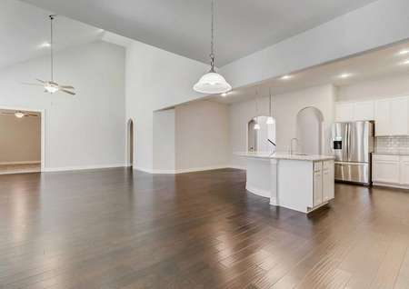 Timberline great room with deep brown floors, light grey finished walls, and white kitchen cabinets