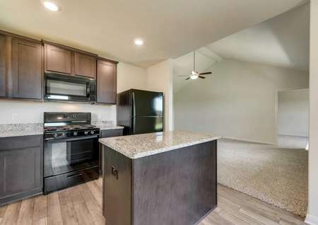 Sabine kitchen and living room with granite counters, island, and modern black appliances