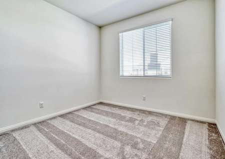 Aster bedroom with brown carpet, white painted basseboards, and gray painted walls
