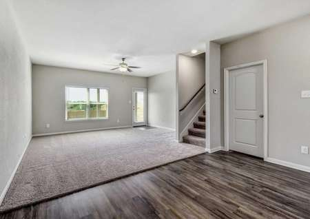 Victoria great room with wood flooring in the dining area, carpeting in the family room, and large windowed door leading to the outside