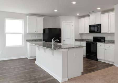 Avery kitchen with white cabinetry, granite island with sink, and walk-in pantry