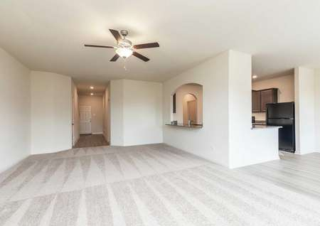 The Osage model's living room, kitchen and entryway. Living room is open with white walls and tan carpet flooring