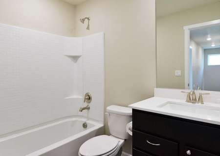 The Northwest Chelan second bathroom is shown with bathtub and shower combo with white quartz countertop.